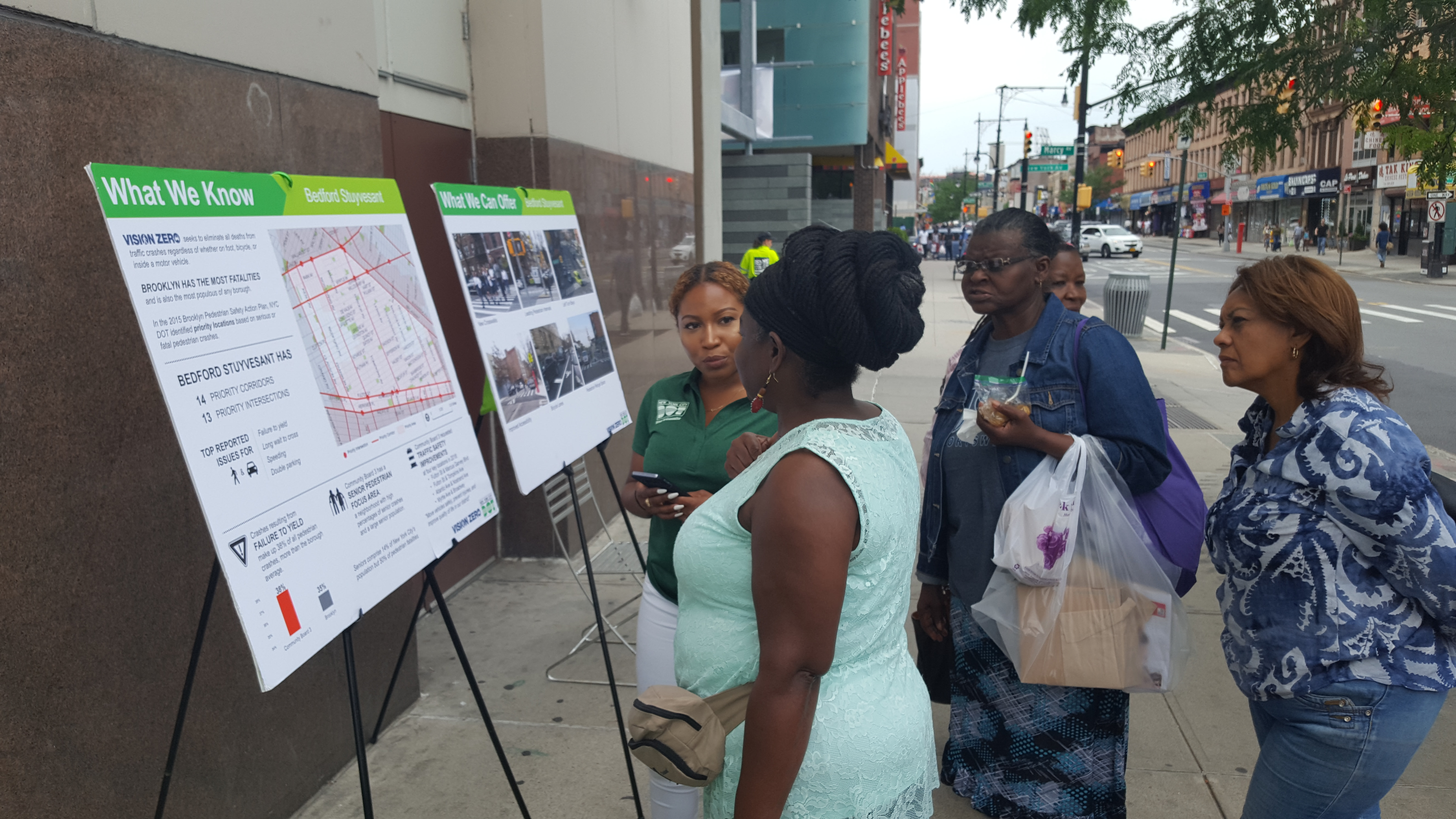 A Street Ambassador talks about transportation safety with folks passing by Restoration Plaza.