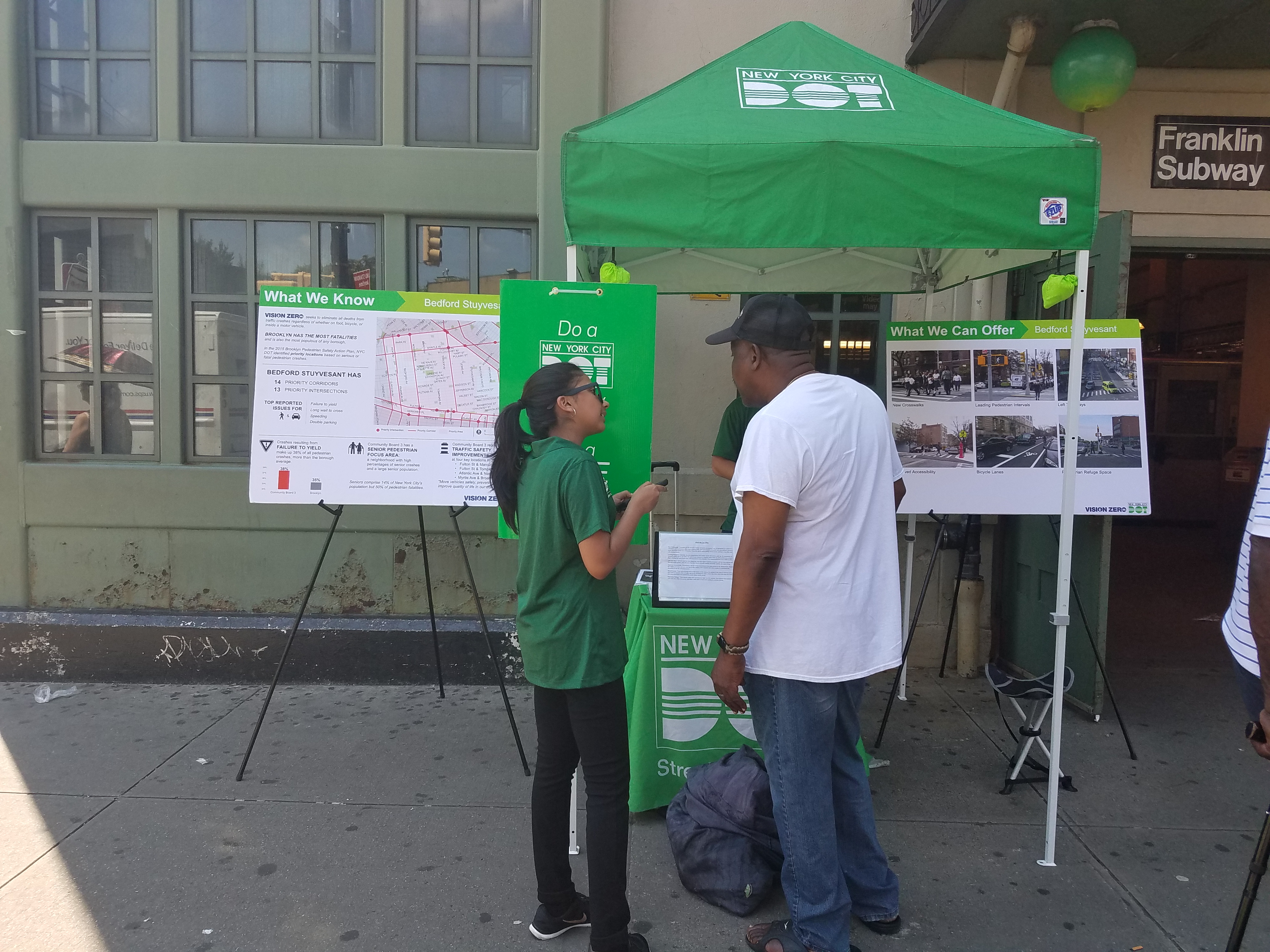 A Street Ambassador chats with a Bed Stuy resident outside the Franklin Ave Subway station.