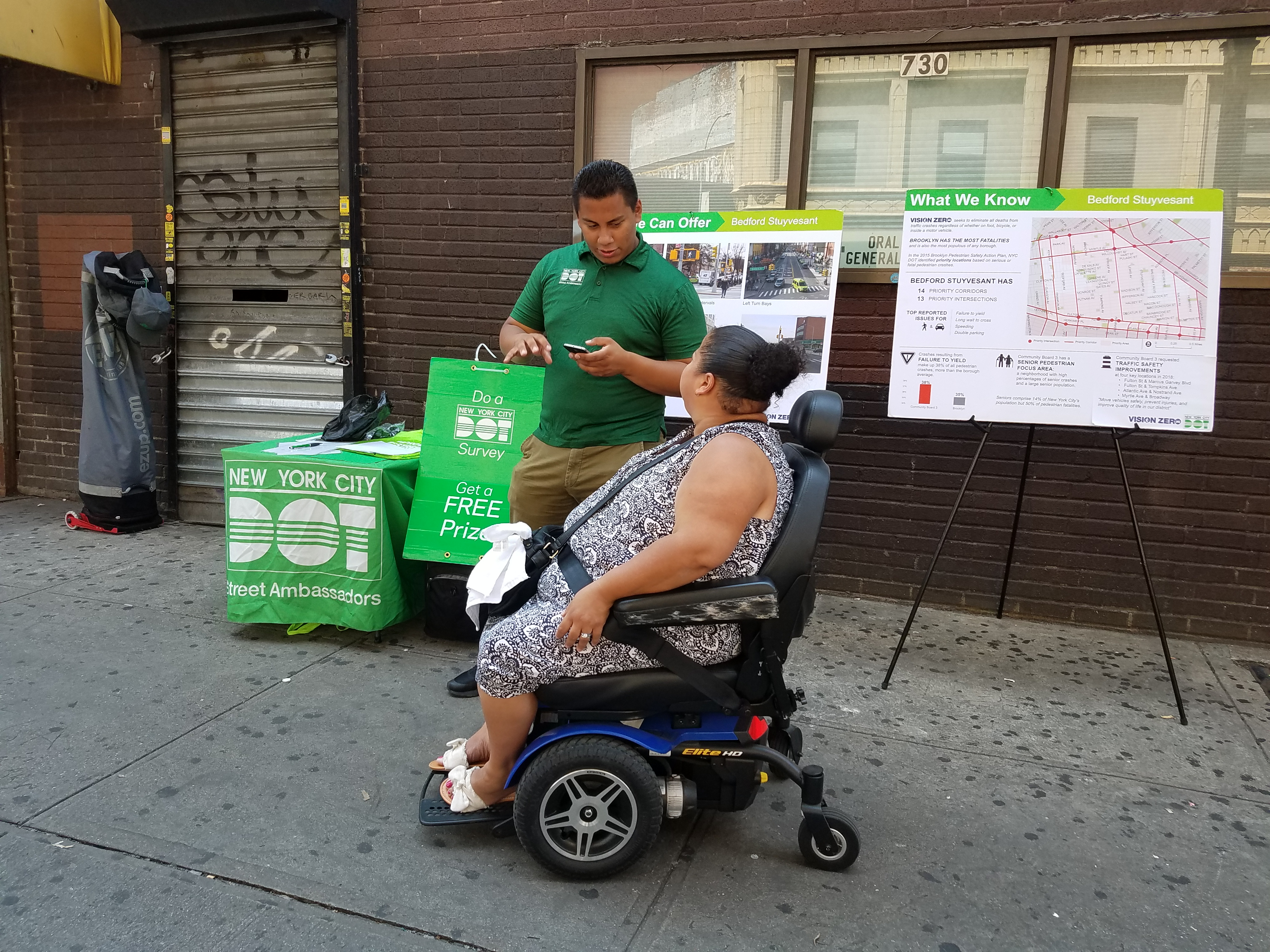 An Ambassador speaks with a person in a motorized wheelchair outside of the Broadway and Flushing JMZ stop.