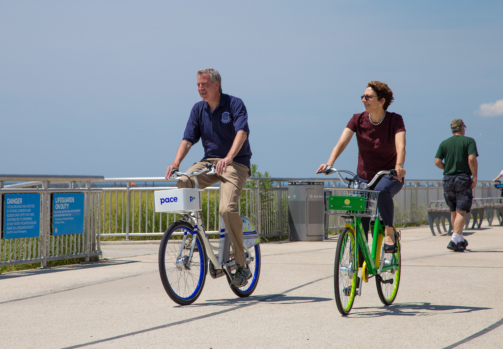 Mayor Bill de Blasio and NYC DOT Commissioner Polly Trottenberg riding the new dockless bike share bikes along the Rockaway boardwalk.