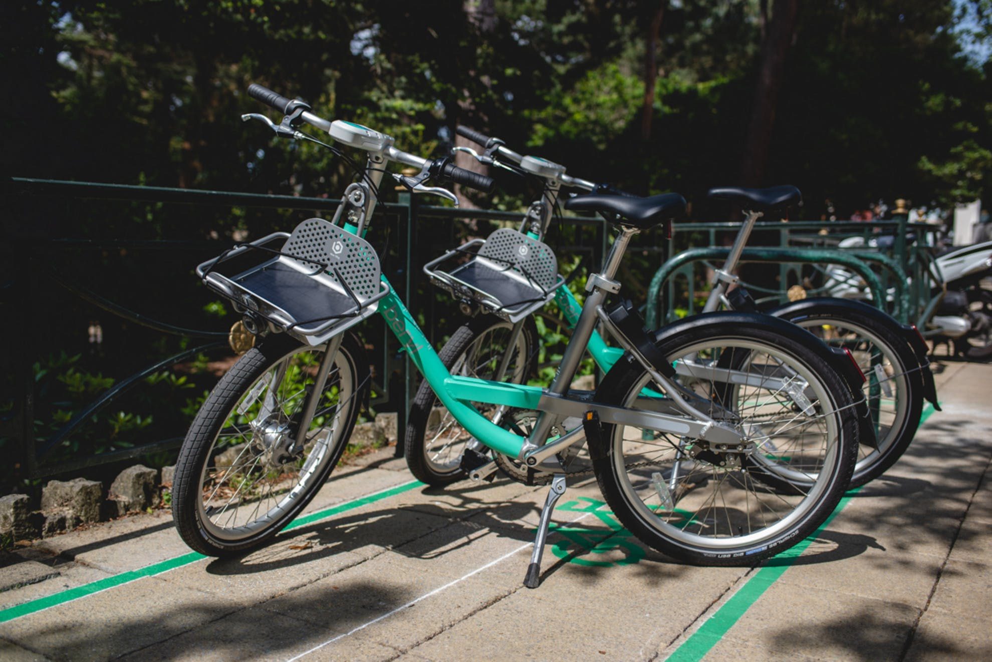 A photo of two Beryl Bikes. They located in Beryl Bays, which are boxes outlined on the sidewalk with paint and tape, signifying that users can park there.