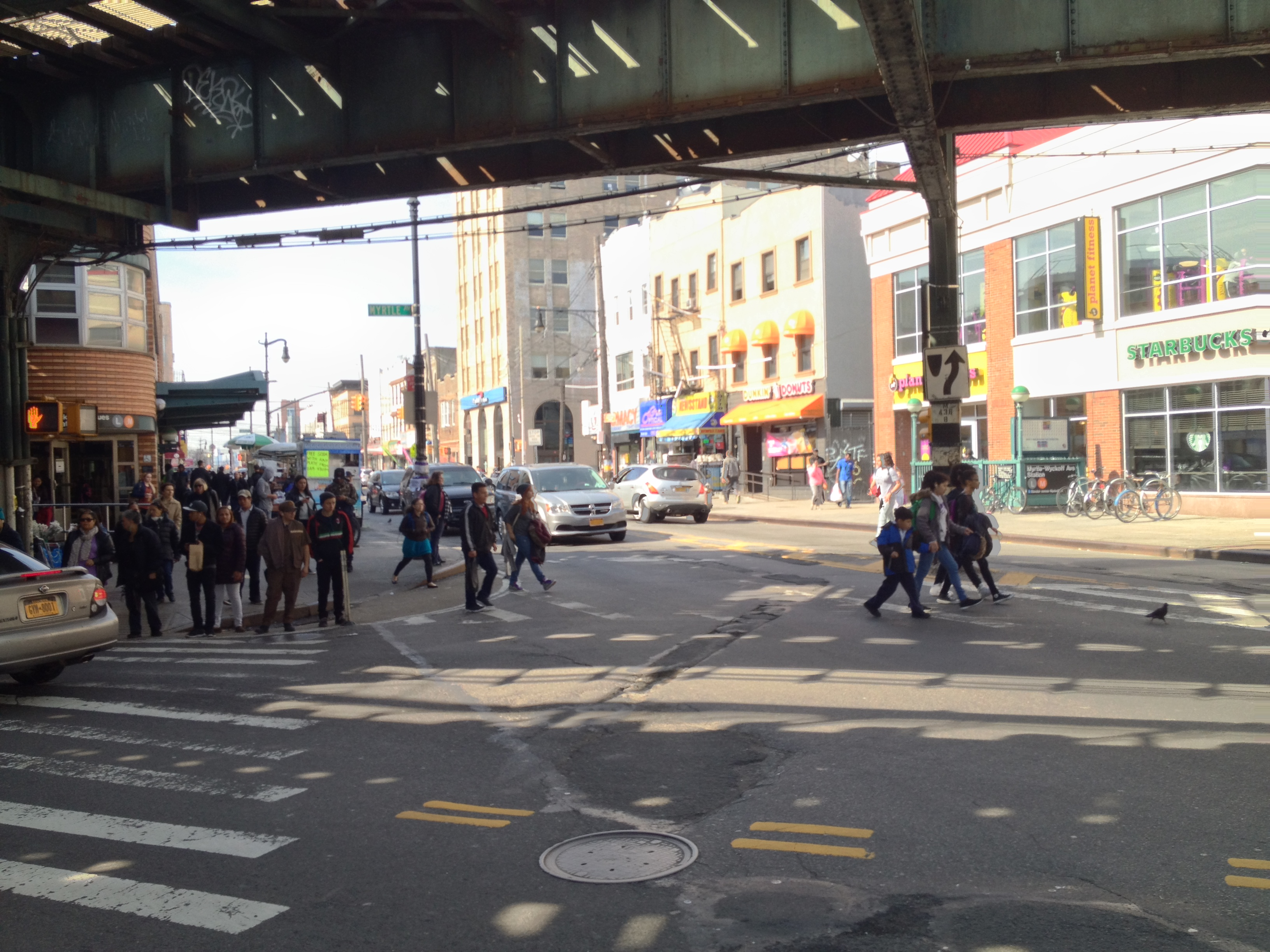 A photo of the intersection of Myrtle/Wyckoff intersection before the plaza. In it, there are crowds of people waiting to cross the street.