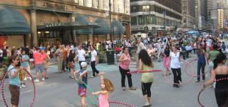 Multiple people in Hearld Square Hula Hooping.
