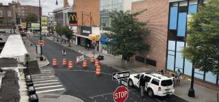 A birds eye view photo of Hillel Place looking towards Flatbush Ave. The area between Kenilworth Pl and Flatbush Ave is closed off from traffic and you can see markings indicating where the new curb and street markings will be by Kenilworth Pl.