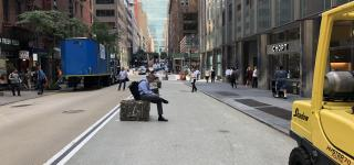 An image of E 43rd Shared St looking towards 3rd Ave. A man can be seen sitting on a granite block lining the new pedestrian space.