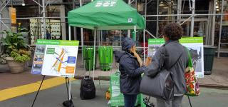 An action photo of a Street Ambassador conducting a survey with a local at Greeley Square.
