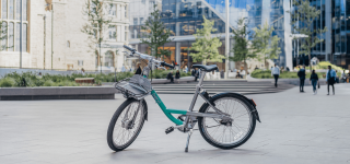 A Beryl Bike in a plaza. The Beryl bike is colored mint green and gray.