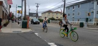 A person riding a Lime bike on the streets of the Rockaways.