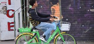 A younger kid riding a Lime Bike in Staten Island.