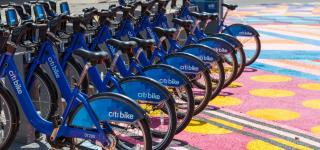 A Citi Bike station parked in the plaza. the Plaza floor is a brightly colored work of art.